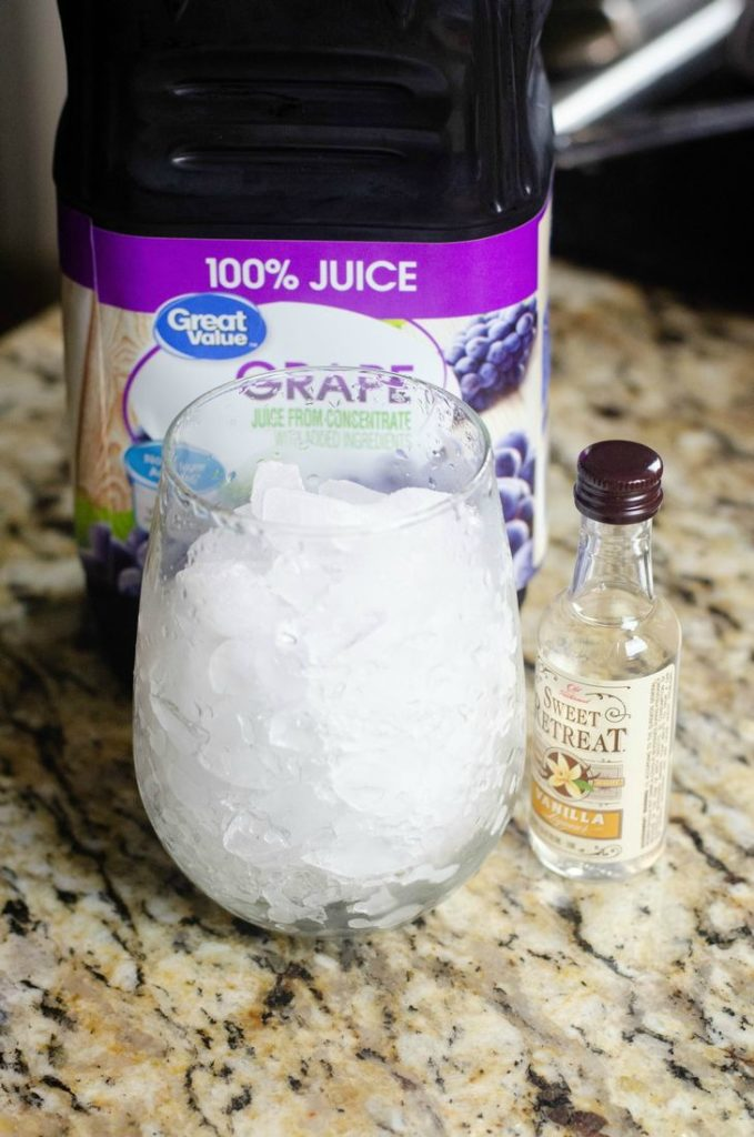 Photo of grape juice with a glass of ice and bottle of  Sweet Retreat Vanilla Liqueur